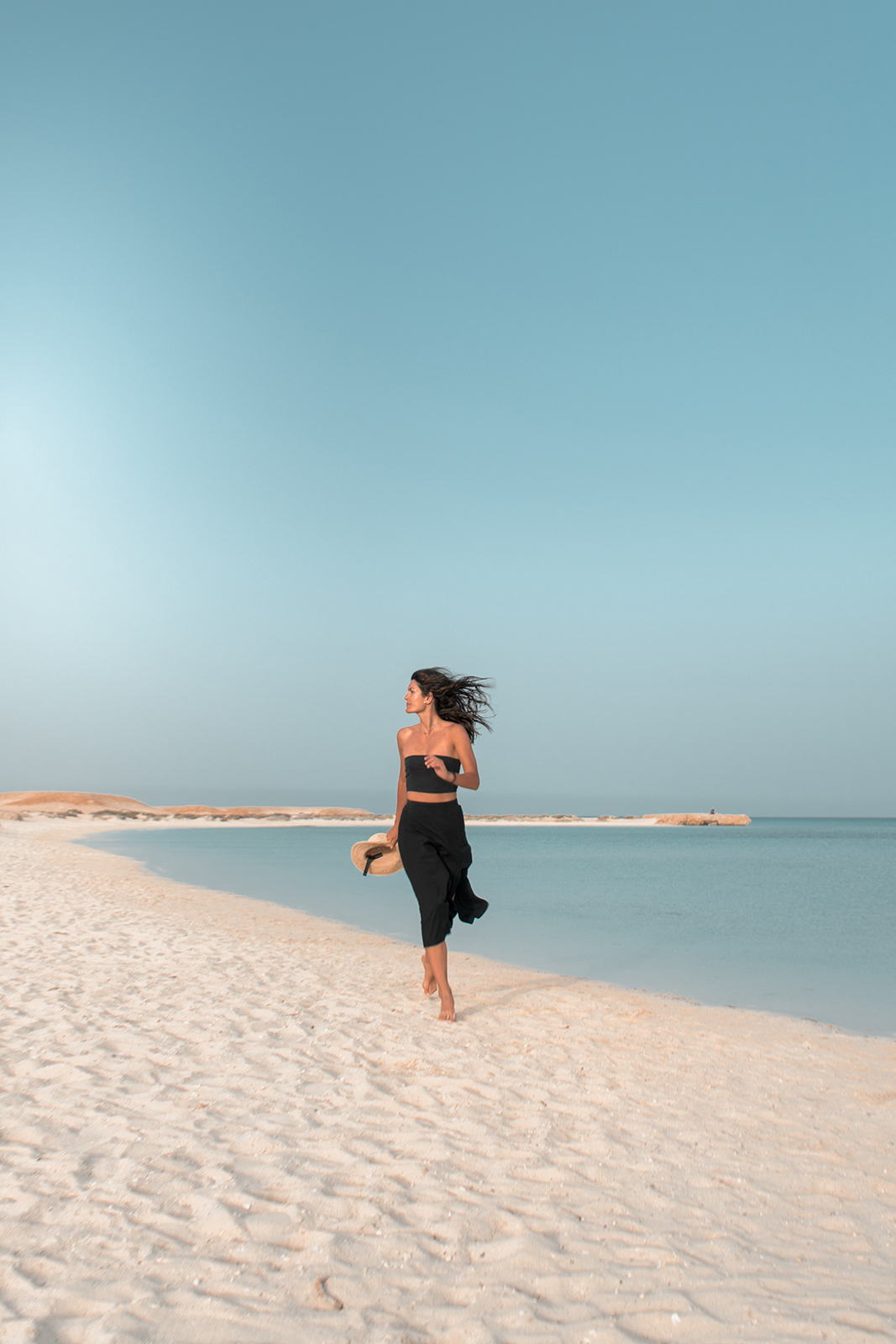 Girl in black running on the beach in Egypt